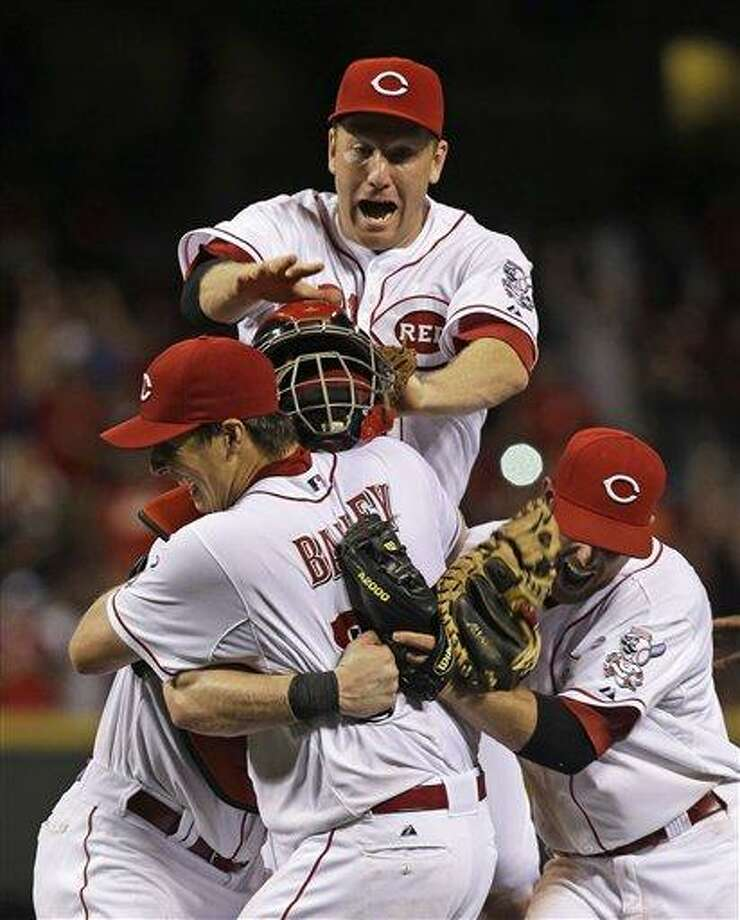 Cincinnati Reds starting pitcher Homer Bailey is mobbed after no-hitting the San Francisco Giants in a baseball game, Tuesday, July 2, 2013, in Cincinnati. (AP Photo/Al Behrman) Photo: AP / AP
