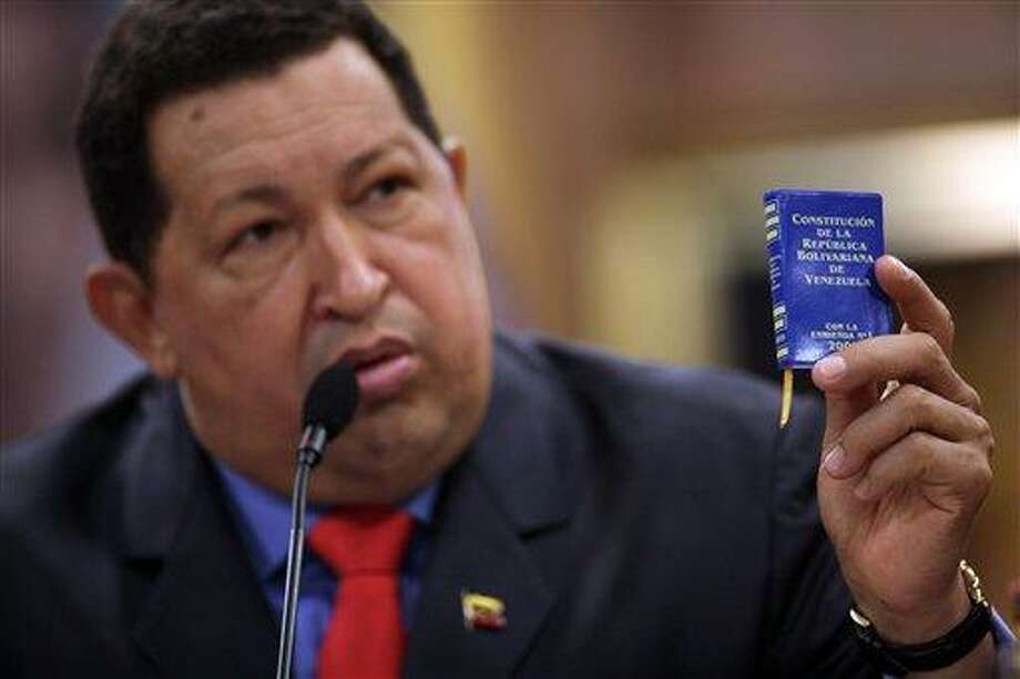 FILE - In this Oct 9, 2012 file photo, Venezuela's President Hugo Chavez holds a miniature copy of his country's constitution during a news conference in Caracas, Venezuela.  The ailing president's health crisis has raised contentious questions ahead of the swearing-in set for Jan. 10, including whether the inauguration could legally be postponed. Officials have raised the possibility that Chavez might not be well enough to take the oath of office, without saying what will happen if he can't. The constitution says that if a president or president-elect dies or is declared unable to continue in office, presidential powers should be held temporarily by the president of the National Assembly and that a new presidential vote should be held within 30 days. (AP Photo/Rodrigo Abd, File) Photo: ASSOCIATED PRESS / AP2012
