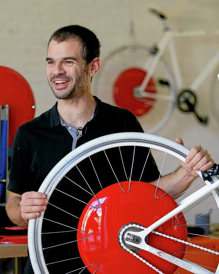 Assaf Biderman, co-inventor of the Copenhagen Wheel and associate director of the SENSEable City Laboratory at MIT, poses with his invention at Superpedestrian, his venture-backed company in Cambridge, Mass. The Copenhagen Wheel is a human/electric hybrid bicycle engine built into a bicycle's back wheel. Pre-orders for the Copenhagen Wheel are being taken with delivery expected by May. Photo: Stephan Savoia — The Associated Press Photos   / AP