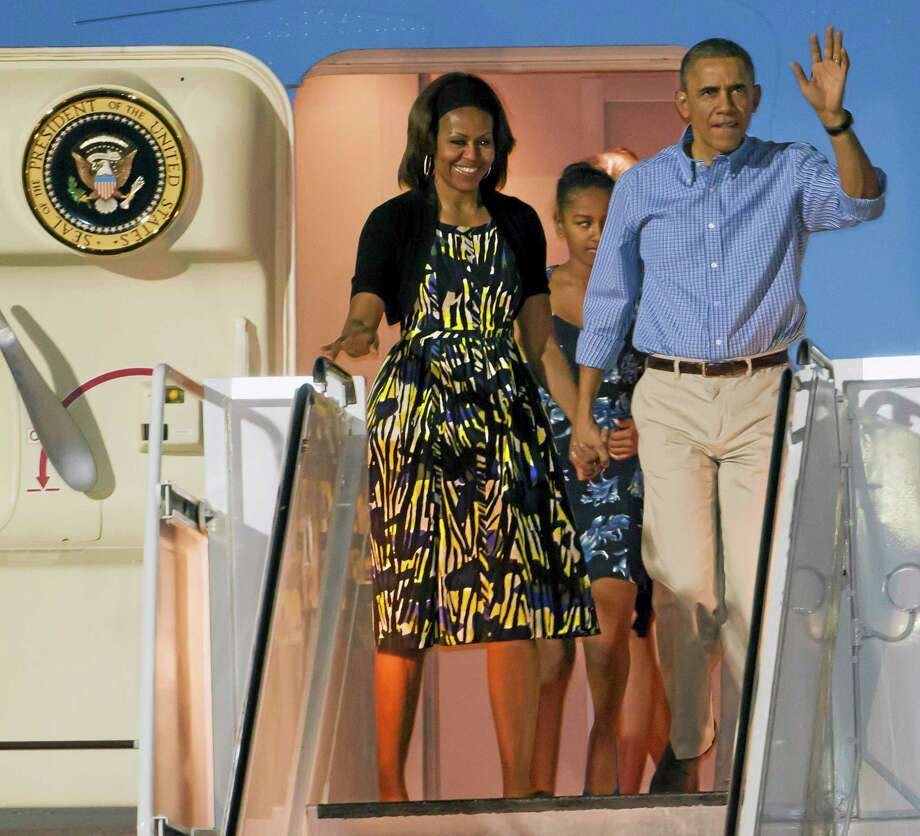 President Barack Obama, right, and first lady Michelle Obama, left, along with their daughter Sasha, center back, disembark Air Force One after arriving at Joint Base Pearl Harbor-Hickam for their family Christmas vacation Friday in Honolulu. Photo: Eugene Tanner — The Associated Press   / FR168001 AP