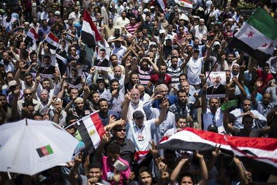 """Supporters of Egypt's Islamist President Mohammed Morsi rally near Cairo University in Giza, Egypt, Tuesday, July 2, 2013. Egypt was on edge Tuesday following a """"last-chance"""" ultimatum the military issued to Mohammed Morsi, giving the president and the opposition 48 hours to resolve the crisis in the country or have the army step in with its own plan.(AP Photo/ Manu Brabo) Photo: AP / AP"""