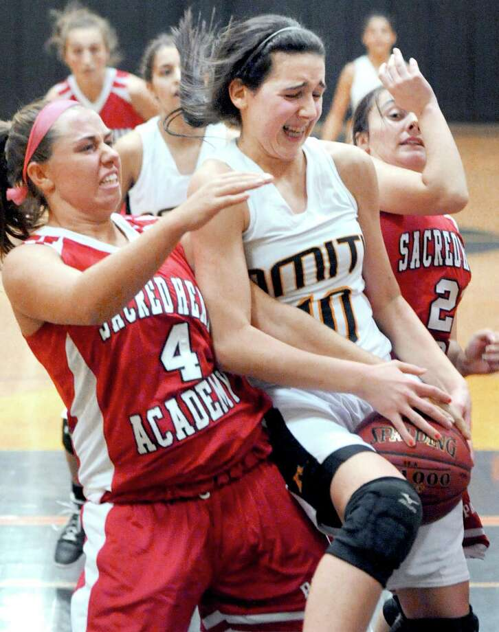 Lexi Caffaso (left) of Sacred Heart Academy reaches in trying to grab a rebound from Marie Papazian (right) of Amity in the second half of a game played earlier this season. SHA beat Cheshire on Wednesday. Photo by Arnold Gold/New Haven Register