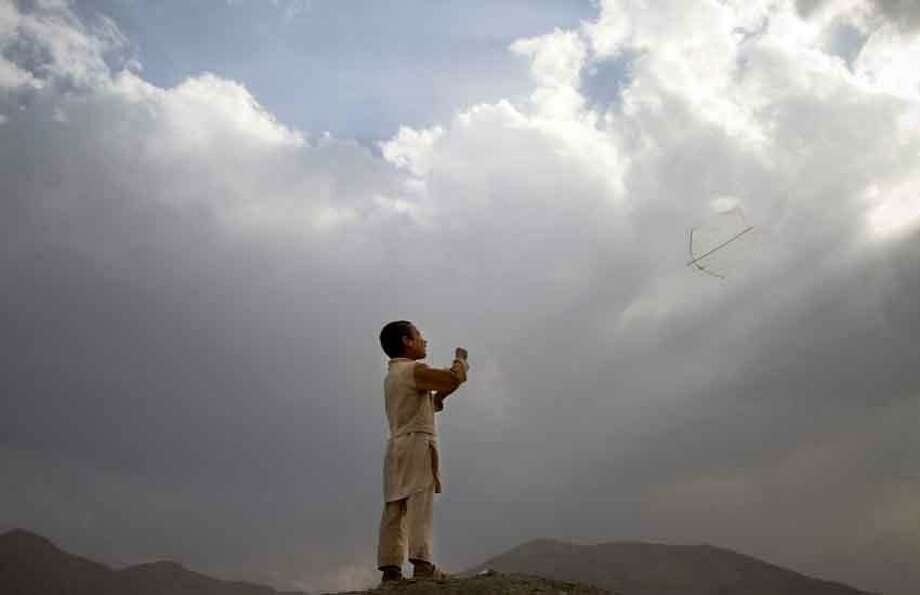 An Afghan boy flies his kite on a hill overlooking Kabul, Afghanistan, Sunday, May 12, 2013. Banned during the Taliban regime, kite flying is once again the main recreational escape for Afghan boys and some men. (AP Photo/Ahmad Jamshid) Photo: ASSOCIATED PRESS / AP2013