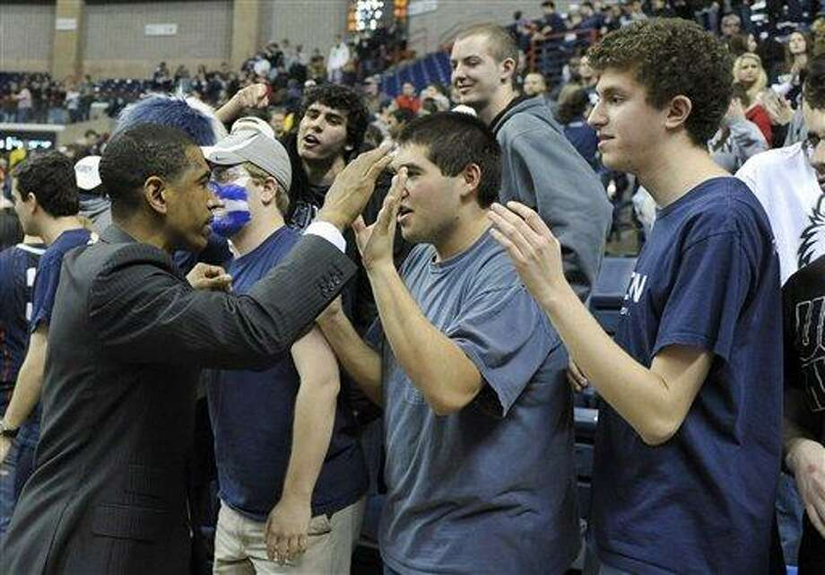 Connecticut coach Kevin Ollie, left, celebrates with fans after his team's 63-59 overtime win against Providence in an NCAA college basketball game in Storrs, Conn., Saturday, March 9, 2013. (AP Photo/Fred Beckham) Photo: AP / FR153656 AP