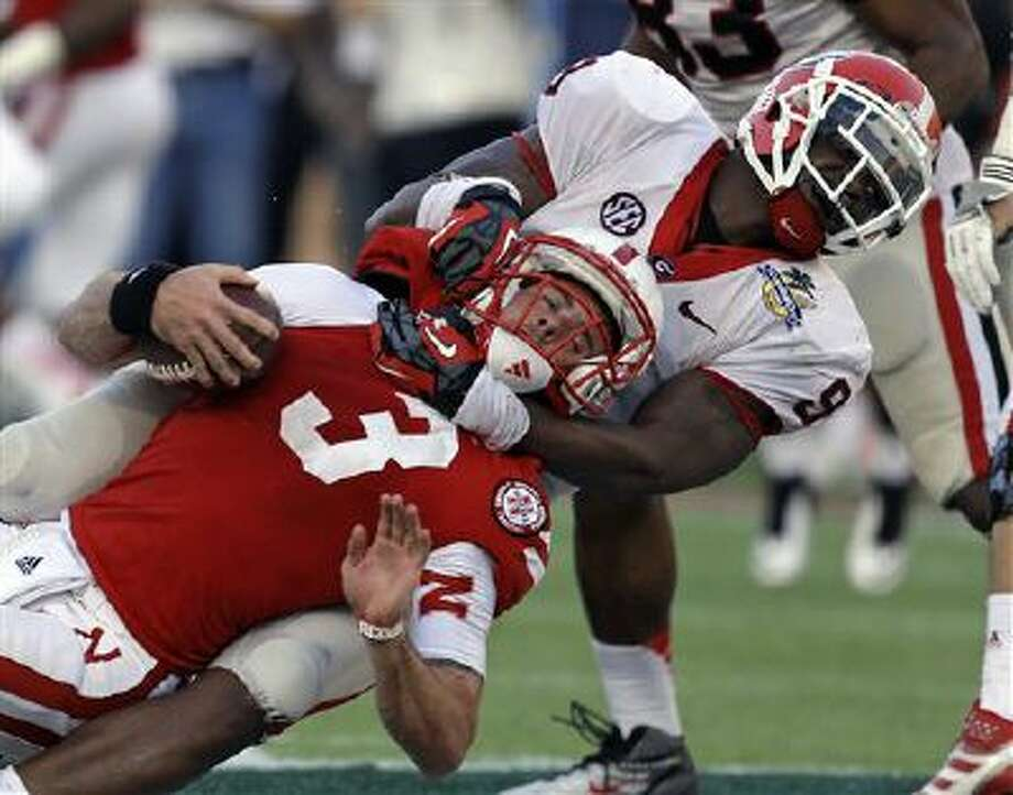 Georgia linebacker Alec Ogletree (9) sacks Nebraska quarterback Taylor Martinez (3) on a fourth and nine play late in the fourth quarter of the Capital One Bowl game last year. This year the teams are rematched in the Gator Bow. Photo: AP / 2013 AP