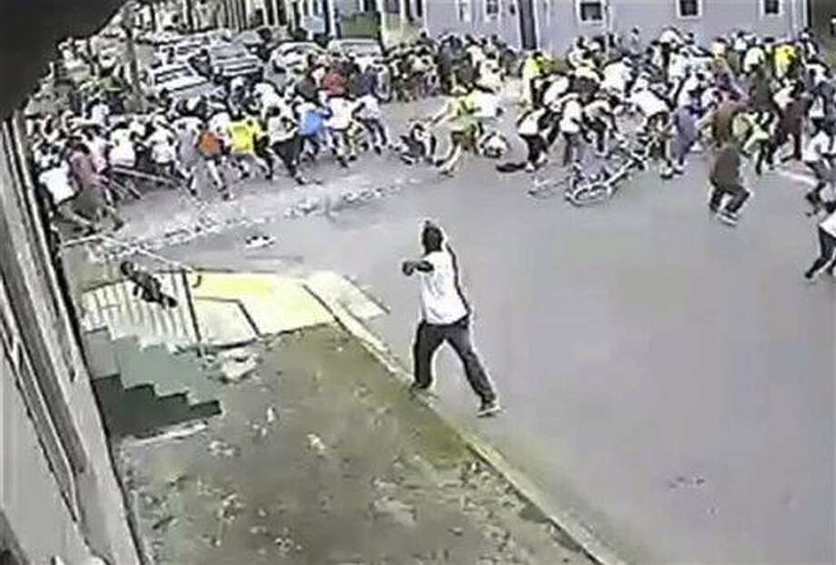 In this image taken from video and provided Monday, May 13, 2013, by the New Orleans Police Department, a possible shooting suspect in a white shirt, bottom center, shoots into a crowd of people, Sunday in New Orleans. The possible suspect may have two accomplices in the Mother's Day gunfire that wounded 19 people during a New Orleans neighborhood parade. (AP Photo/New Orleans Police Department) Photo: AP / New Orleans Police Department
