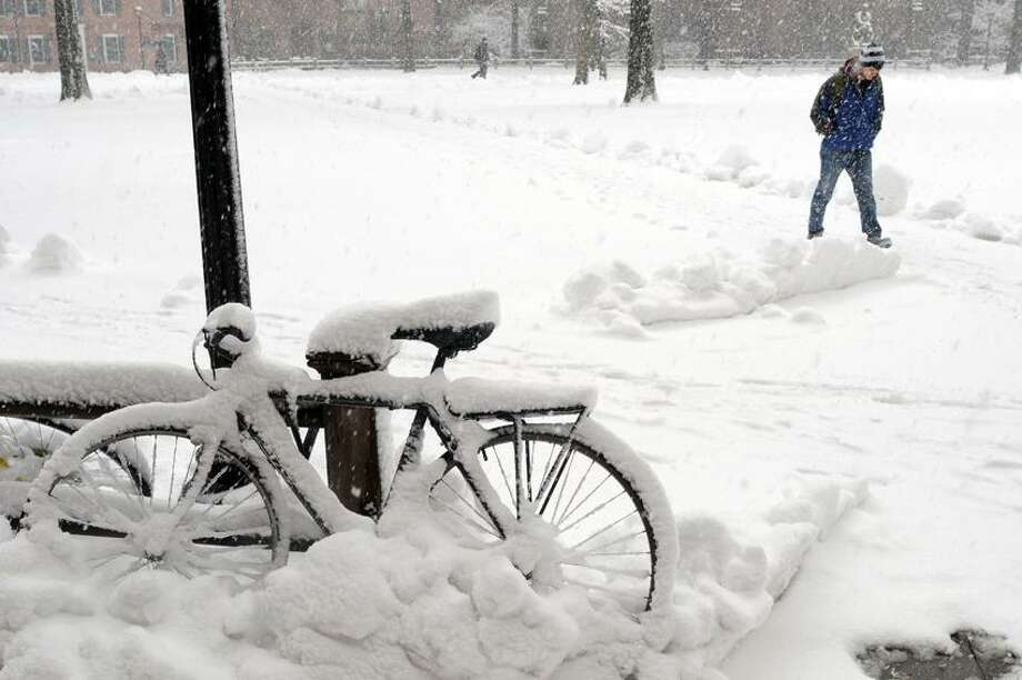 A student at Yale University in New Haven, Connecticut uses his feet as transportation on the Old Campus as a bicycle nearby, covered by snow, sits idle during the snowstorm Friday morning March 8, 2013. Photo by Peter Hvizdak / New Haven Register Photo: New Haven Register / ©Peter Hvizdak /  New Haven Register