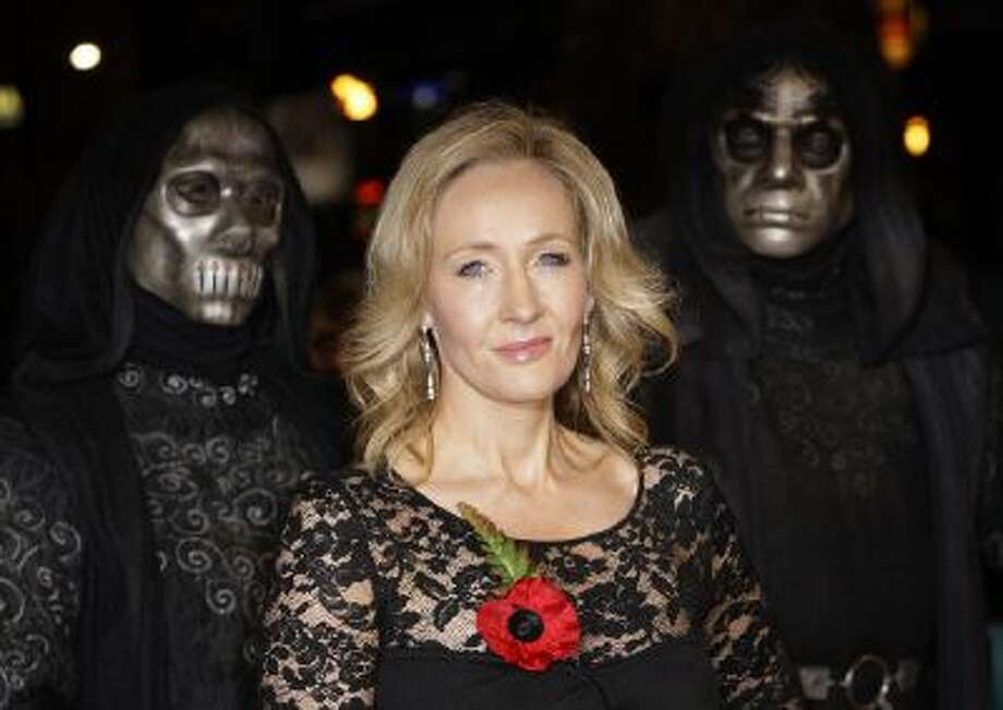 British author J K Rowling arrives at a cinema in London's Leicester Square for the World Premiere of Harry Potter and the Deathly Hallows Part 1, as masked actors stand behind, Nov. 11, 2010.