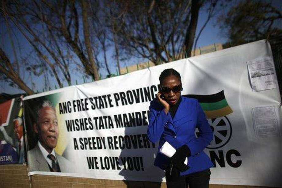 """A woman talks on a mobile phone in front of a poster displayed on a fence in support of former South African President Nelson Mandela at the entrance of the Mediclinic Heart Hospital where Mandela is being treated in Pretoria, South Africa, Tuesday, July 2, 2013. The South African government said Monday that Mandela remains in """"critical but stable"""" condition in the hospital where he was admitted on June 8. (AP Photo/Markus Schreiber) Photo: AP / AP"""