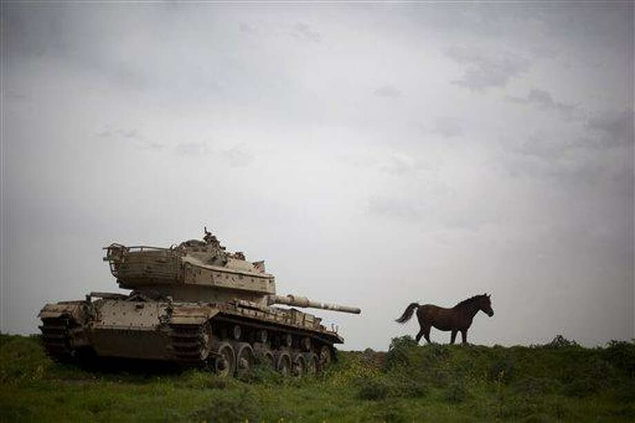 A horse runs in a pasture next to an old Israeli tank in the Israeli-controlled Golan Heights on the border with Syria, Friday, March 8, 2013. Israel captured the Golan from Syria in 1967 Mideast war. (AP Photo/Ariel Schalit) Photo: AP / AP