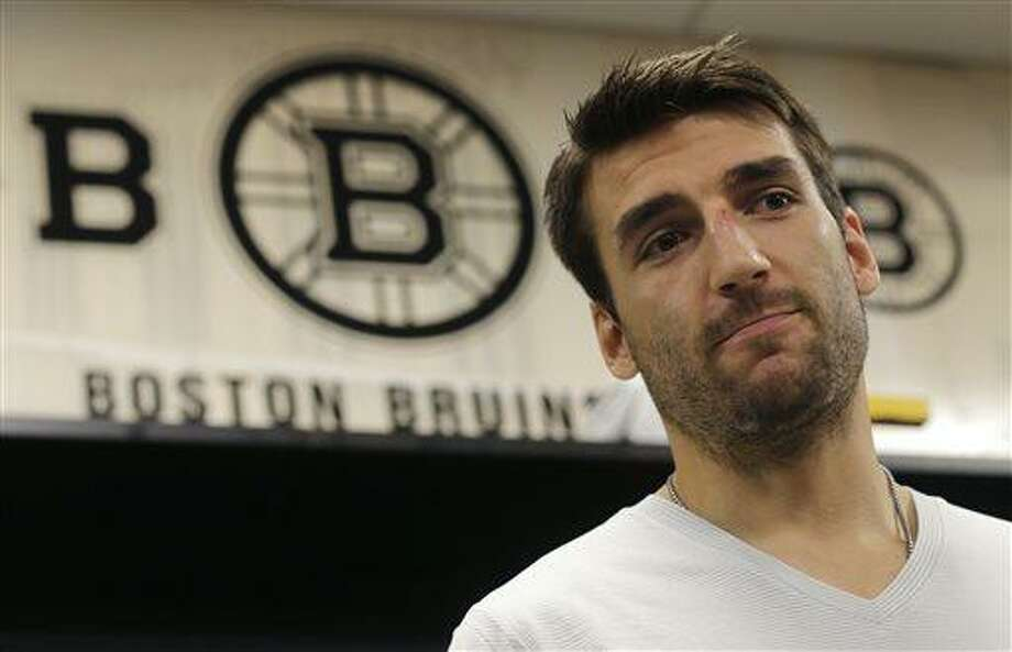 Boston Bruins center Patrice Bergeron talks with reporters in the team locker room, Tuesday, July 2, 2013, in Boston. Bergeron played through a multiple injuries including a broken rib, separated shoulder and hole in his lung during the Stanley Cup Championship. (AP Photo/Charles Krupa) Photo: AP / AP