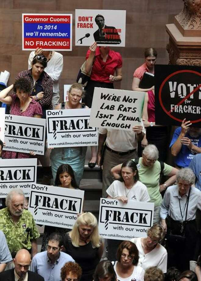 "FILE - In this June 20, 2012 file photo, protesters rally against the oil and gas drilling method known as hydraulic fracturing, or ""fracking,"" as the legislative session winds down at the Capitol in Albany, N.Y. The health study cited by leading environmentalist Robert F. Kennedy Jr. as a turning point in helping persuade Gov. Andrew Cuomo to scrap plans for a limited fracking pilot program is not expected to be the defining study on whether fracking is safe, according to researchers involved in the project and other independent experts.  (AP Photo/Tim Roske, File) Photo: AP / FR61503 AP"