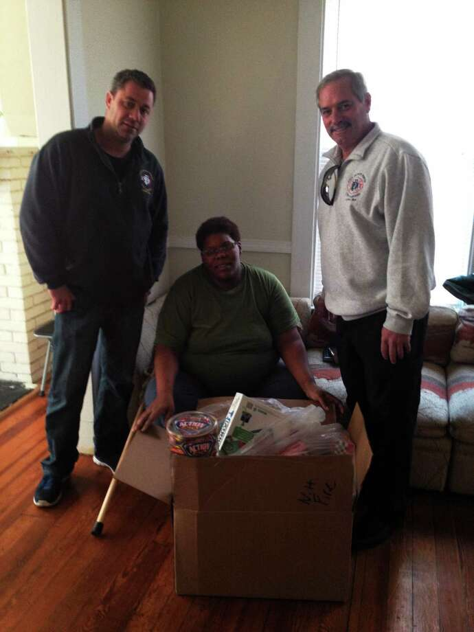 Firefighter Danny Coughlin and Fire Union President Lt. James Kottage drop off toys to mother of family who lost Christmas toys in a burglary. Submitted photo. Photo: Journal Register Co.