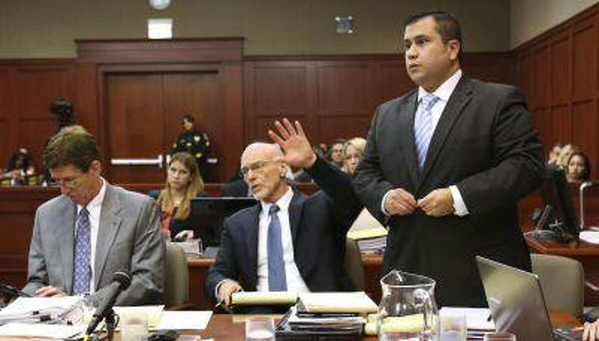 George Zimmerman stands next to his attorneys, Mark O'Mara (L), and Don West (C), to be identified by state witness Chris Serino, a Sanford police officer, in his second degree murder trial in Seminole circuit court in Sanford, Florida, July 1, 2013. (Joe Burbank/Reuters/Pool)