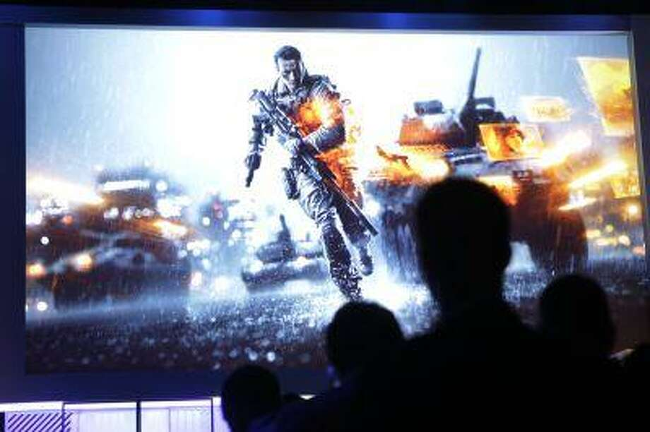 Attendees watch a presentation on video game Battlefield 4 at the Microsoft Xbox E3 media briefing in Los Angeles, Monday, June 10, 2013. Microsoft focused on how cloud computing will make games for its next-generation Xbox One console more immersive during its Monday presentation at the Electronic Entertainment Expo. (AP Photo/Jae C. Hong) Photo: ASSOCIATED PRESS / AP2013