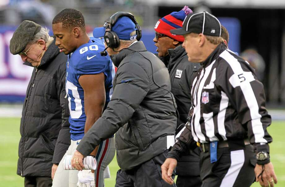 Giants wide receiver Victor Cruz walks off the field with head coach Tom Coughlin, center left, during the second half of Sunday's game against the Seattle Seahawks in East Rutherford, N.J. Photo: Peter Morgan — The Associated Press   / AP