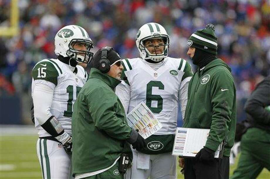 New York Jets quarterbacks Tim Tebow (15) and Mark Sanchez (6) talk on the sidelines with offensive coordinator Tony Sparano (center) during the second half an NFL football game against the Buffalo Bills on Sunday, Dec. 30, 2012, in Orchard Park, N.Y. (AP Photo/Bill Wippert) Photo: ASSOCIATED PRESS / AP2012
