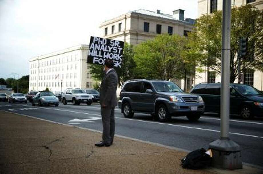 Matthew Giarmo of Alexandria, Virginia, who lost his contract job with the Department of Health and Human Services in 2012, holds up a sign seeking a job with a lower salary than he would normally ask on a street corner October 8, 2013 in Washington, DC. With his wife furloughed from her job at the Smithsonian Institution due to the U.S. government shutdown, Giarmo, who has a Ph.D. in social-personality psychology, said he had no choice but to stand on the street to find work. (Alex Wong/Getty) Photo: Getty Images / 2013 Getty Images