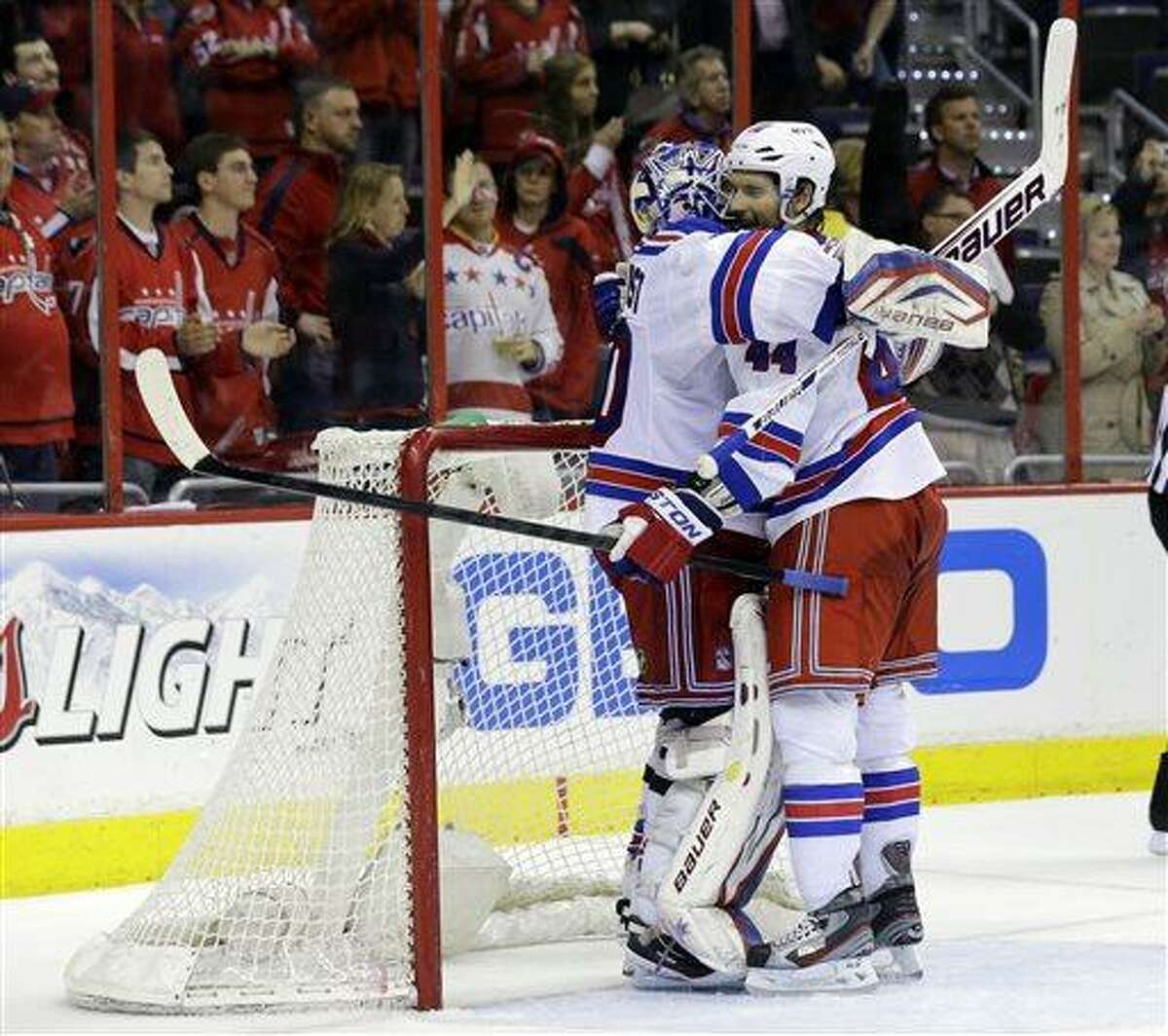 New York Rangers goalie Henrik Lundqvist (30), from Sweden, celebrates with defenseman Steve Eminger (44) after Game 7 first-round NHL Stanley Cup playoff hockey series against the Washington Capitals, Monday, May 13, 2013 in Washington. The Rangers won 5-0. (AP Photo/Alex Brandon)