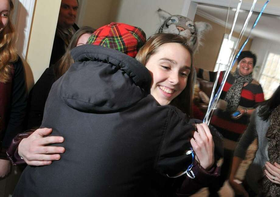 Cheshire--Miura Wiley, 13, gets a hug from neighbor Bonnie Bouman, after she was awarded the Cheshire Town Scholar award in her home by Cheshire Academy. They surprised the outstanding student as she arrived home off the school bus. In the rear is Kristen Mariotti of Cheshire Academy admissions who was on hand to deliver the award.  Photo-Peter Casolino 03/07/12
