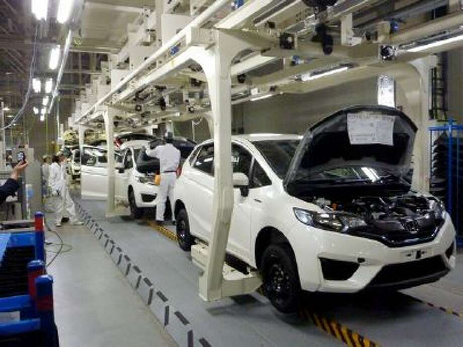 In this Nov. 7, 2013 photo, workers assemble cars at Honda Motor Co.'s factory in Yorii, Saitama prefecture, Japan.