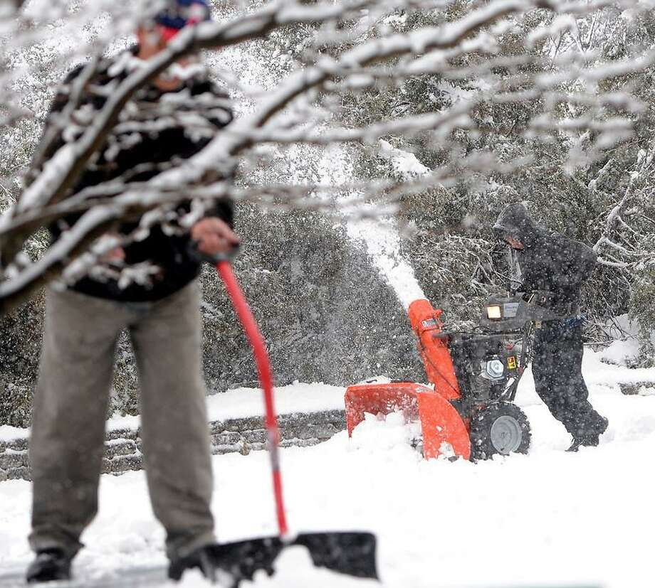 Danny Tran of Branford, right, uses a snowblower to clear the parking lot of snow from Glamour Nails II business on Main Street in  Branford, Connecticut  during the snowstorm Friday morning March 8, 2013. Photo by Peter Hvizdak / New Haven Register Photo: New Haven Register / ©Peter Hvizdak /  New Haven Register