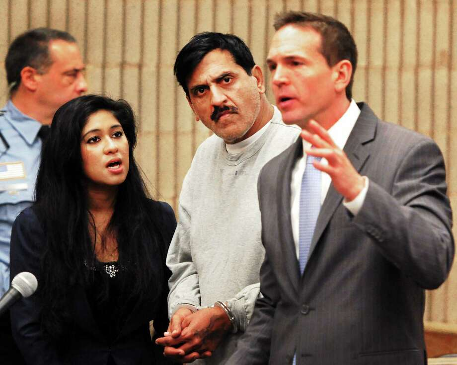 Muhammad Chaudhry, 51, of West Haven, center, charged with throwing hot oil on his estranged wife, appears at his arraignment with an interpreter, left, and Senior Assistant Public Defender Kenneth Bunker, right, Thursday at Superior Court in Milford. Chaudhry faces one count each of first-degree assault and criminal attempt to commit first-degree assault. Photo: Peter Hvizdak — New Haven Register     / ©Peter Hvizdak /  New Haven Register