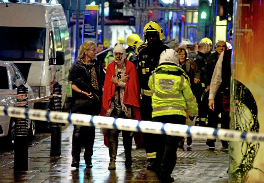"""A woman stands bandaged and wearing a blanket  given by emergency services  following an incident at the Apollo Theatre, in London's Shaftesbury Avenue, Thursday evening, Dec. 19, 2013, during a performance at the height of the Christmas season, with police saying there were """"a number"""" of casualties. It wasn't immediately clear if the roof, ceiling or balcony had collapsed  during a performance. Police said they """"are aware of a number of casualties,"""" but had no further details. (AP Photo by Joel Ryan, Invision) Photo: AP / INVISION"""