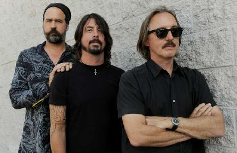 """In this Sept. 6, 2011 photo, Krist Novoselic, left, and Dave Grohl, center, former members of the band Nirvana, pose with Butch Vig, producer of the band's landmark 1991 album """"Nevermind,"""" poses in Los Angeles."""