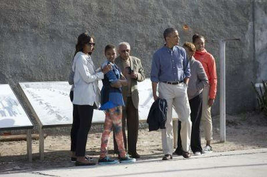 From left, first lady Michelle Obama, Sasha Obama, Ahmed Kathrada former prisoner with Nelson Mandela guiding the tour, U.S. President Barack Obama, Marian Robinson and Leslie Robinson, look out over the courtyard of the prison on Robben Island, South Africa, Sunday, June 30, 2013. Former South African president Nelson Mandela spent 18 years of his 27-year prison term on the island locked up by the former apartheid government. (AP Photo/Carolyn Kaster) Photo: ASSOCIATED PRESS / AP2013