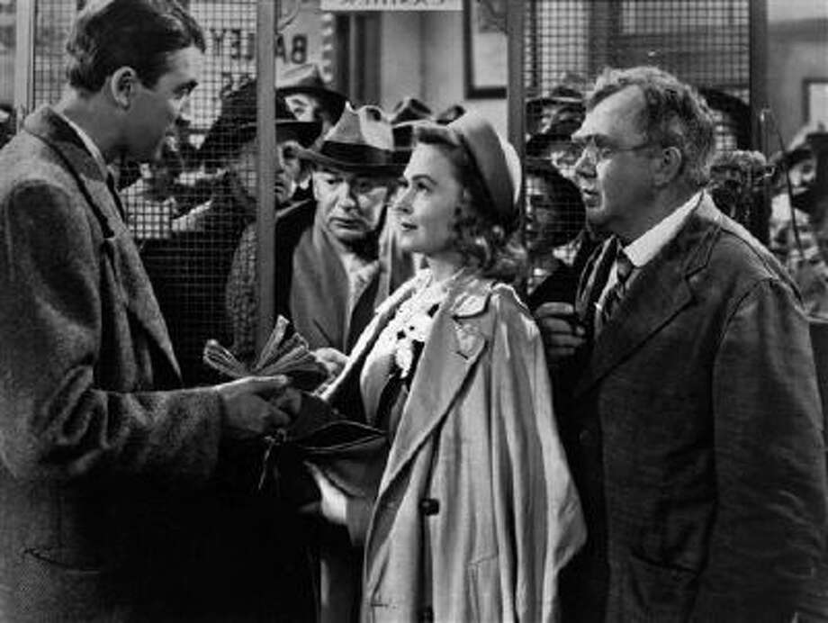"In this undated file photo James Stewart, left, Thomas Mitchell, right, and Donna Reed appear in a scene from the 1946 film ""It's A Wonderful Life."" Folks in Seneca Falls, N.Y., think Bailey's make-believe hometown, Bedford Falls in the movie, was heavily inspired by their quaint upstate town. This cannot be proven, and director Frank Capra never confirmed such a connection, but that hasn't stopped locals in Seneca Falls from celebrating the beloved movie every December. Photo: AP / AP"