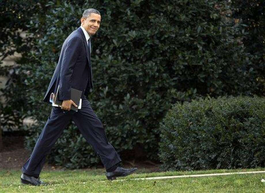 President Barack Obama looks to the media as he walks to the Oval Office of the White House as he returns from greeting members of the staff, Tuesday, Dec. 18, 2012, in Washington. (AP Photo/Carolyn Kaster) Photo: AP / AP