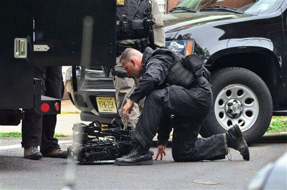 A state police swat team member readies a robot to enter a home where a man had barricaded himself on Friday, May 10, 2013 in Trenton, N.J.  The standoff with an armed man who police said took multiple hostages entered its second day Saturday as authorities worked to negotiate his surrender and his captives' safe release. The man, whose identity has not been released, was holed up in a brick house in South Trenton more than 18 hours after the standoff began Friday afternoon, authorities said.   (AP Photo/The Trentonian, Scott Ketterer)  TRENTON TIMES OUT; PHILLY METRO OUT Photo: AP / The Trentonian