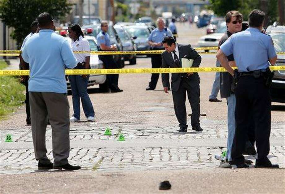 New Orleans police officers investigate the scene at the intersection of Frenchmen and N. Villere Streets in New Orleans after gunfire at a Mother's Day second-line parade on Sunday, May 12, 2013. Police spokeswoman Remi Braden said in an email that many of the 17 victims were grazed and most of the wounds weren't life-threatening. No deaths were reported. (AP Photo/The Times-Picayune, Michael DeMocker) Photo: AP / The Times-Picayune