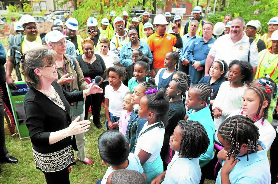 The Lincoln Bassett Soaring Eagles Choir sings under the direction of Sara Suitor, left, during a groundbreaking for a greenhouse at the community garden on Shelton Avenue and Ivy Street in New Haven Wednesday. Photo: Arnold Gold — New Haven Register
