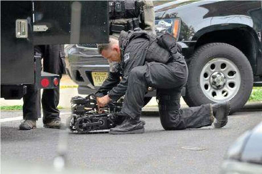 State police prepare a robot to observe the scene during a tense hostage situation in the city on Friday.