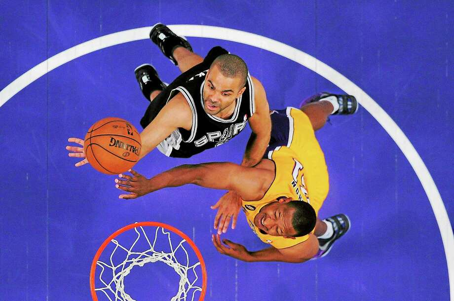 San Antonio Spurs guard Tony Parker, left, puts up a shot as Los Angeles Lakers guard Chris Duhon defends during the first half in Game 3 of the first round of the Western Conference playoffs on April 26 in Los Angeles. Photo: Mark J. Terrill — The Associated Press   / Mark J. Terrill2013