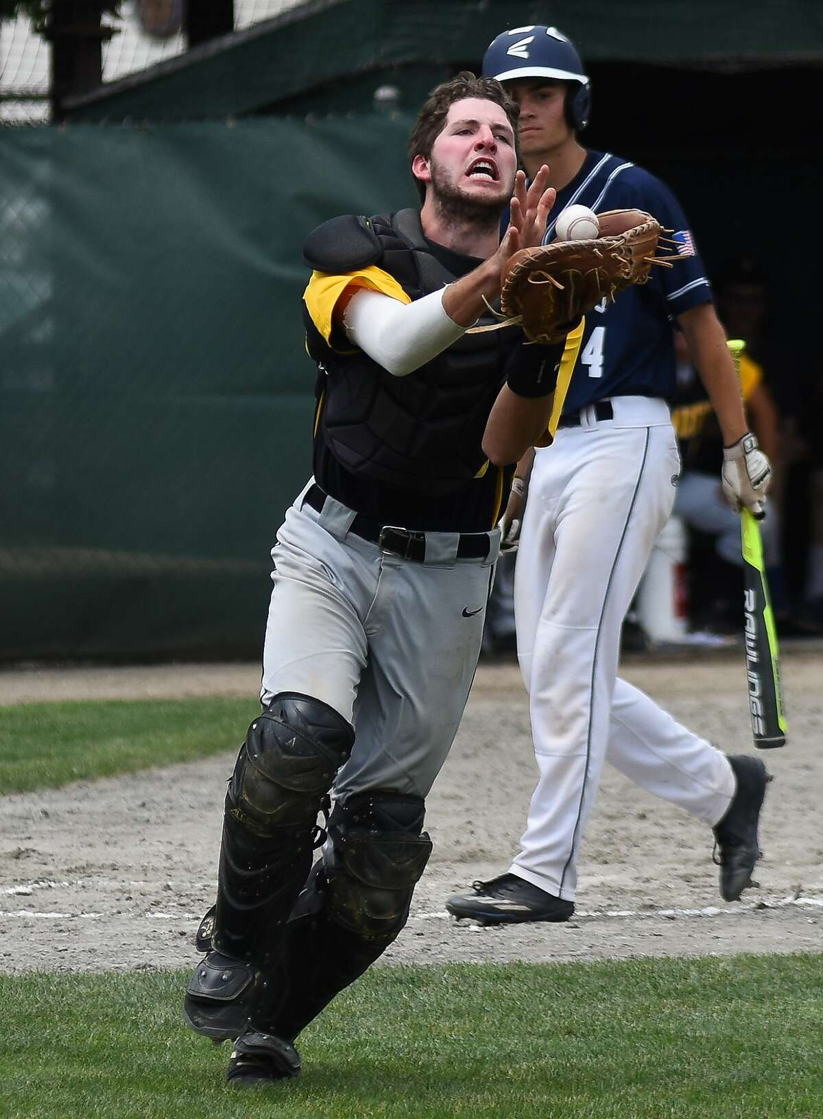 Amity catcher Pat Winkel, front, extends to catch a pop up bunted by Staples' Max Popken, rear, during Saturday's Class LL championship game at Palmer Field in Middletown.