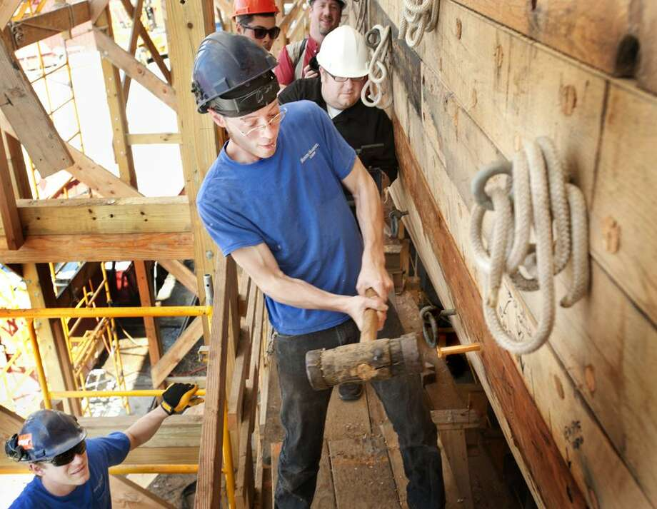 MYSTIC-Shipwright, Sean Kelly, hammers the Golden Spike into the final plank of the 1841 whaleship Charles W. Morgan. The plank is known as the shutter plank because it shuts in and completes the hull. The achievement  is traditrionally a moment of celebration in the shipbuilding process. The Morgan has been undergoing restoration since 2008. The resotoration is scheduled to be completed in May of 2014.    Melanie Stengel/Register