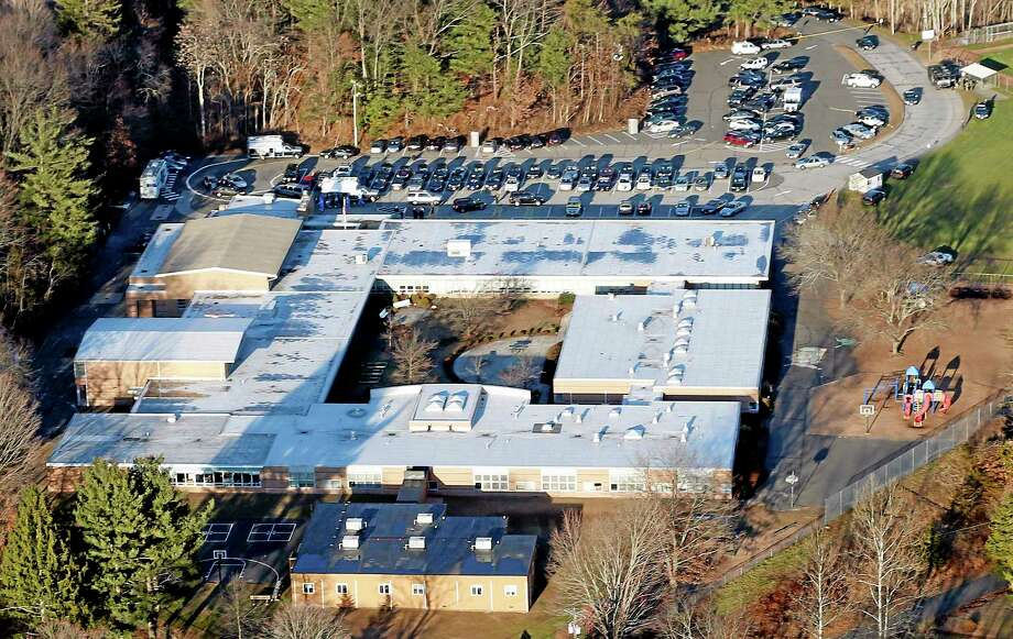 FILE - This Dec. 14, 2012 aerial file photo shows Sandy Hook Elementary School in Newtown, Conn. Contractors demolishing Sandy Hook Elementary School are being required to sign confidentiality agreements forbidding public discussion of the site, photographs or disclosure of any information about the building where 26 people were fatally shot in December 2012. (AP Photo/Julio Cortez, File) Photo: AP / AP