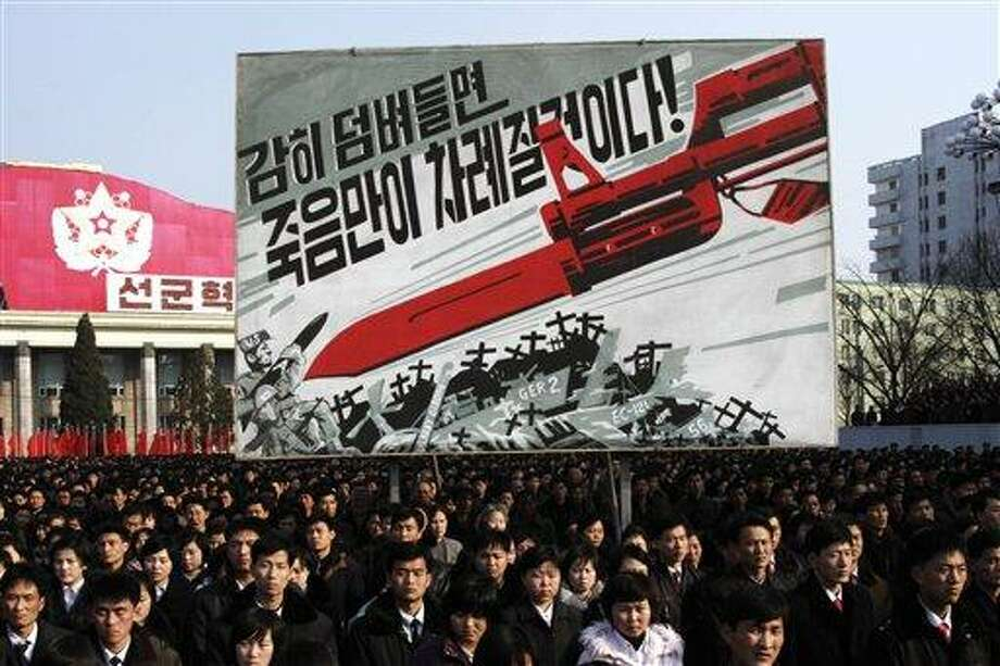 """North Koreans attend a rally to support a statement given on Tuesday by a spokesman for the Supreme Command of the Korean People's Army vowing to cancel the 1953 cease-fire that ended the Korean War as well as boasting of the North's ownership of """"lighter and smaller nukes"""" and its ability to execute """"surgical strikes""""  meant to unify the divided Korean Peninsula, at Kim Il Sung Square in Pyongyang, North Korea, on Thursday, March 7, 2013. North Korea on Thursday vowed to launch a pre-emptive nuclear strike against the United States, amplifying its threatening rhetoric hours ahead of a vote by U.N. diplomats on whether to level new sanctions against Pyongyang for its recent nuclear test. The billboard in background depicts a large bayonet pointing at U.S. army soldiers with writing reading """"If you dare invade, only death will be waiting for you!"""" (AP Photo/Jon Chol Jin) Photo: AP / AP"""