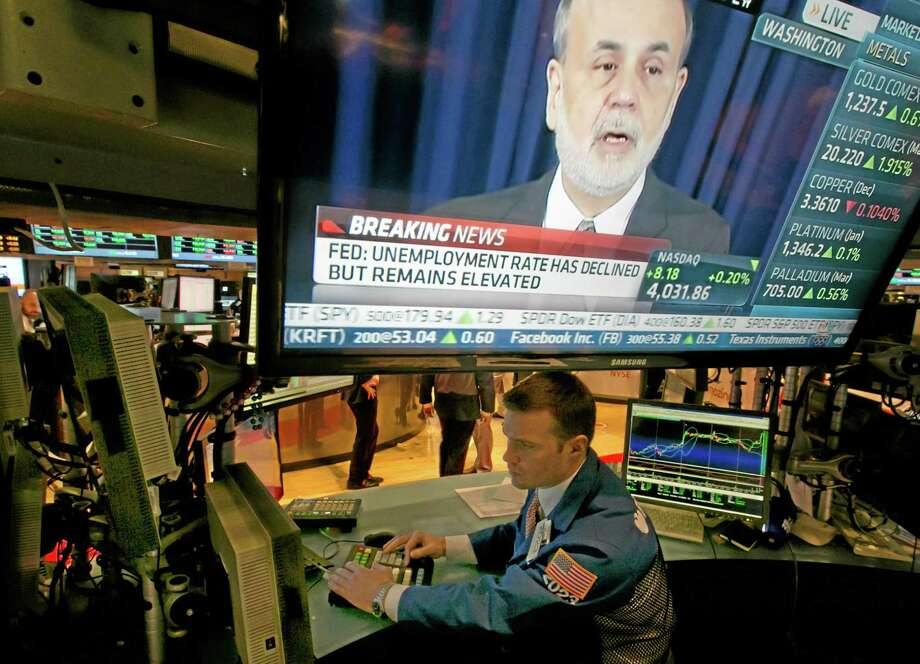 The news conference of Federal Reserve Chairman Ben Bernanke appears on a television screen at a trading post on the floor of the New York Stock Exchange, Wednesday, Dec. 18, 2013. The Federal Reserve has decided to reduce its stimulus for the U.S. economy because the job market has shown steady improvement. The Fed will trim its $85 billion a month in bond purchases by $10 billion starting in January.  (AP Photo/Richard Drew) Photo: AP / AP
