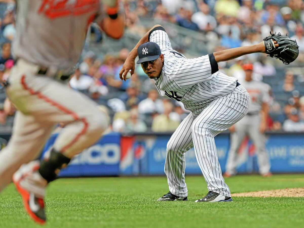 New York Yankees starting pitcher Ivan Nova attempts to throw out the Orioles' Nate McLouth at first base during the ninth inning Saturday.