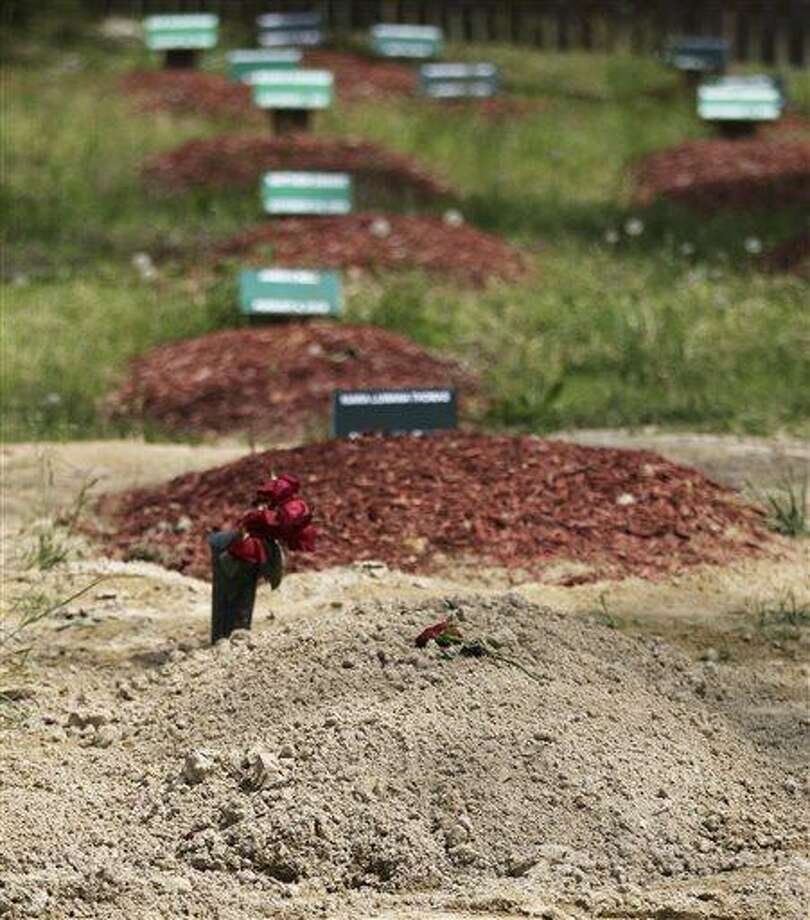 ADDS THAT TSARNAEV'S GRAVE IS ONE OF TWO NEWLY DUG GRAVES AT THE CEMETERY - Flowers are placed on one of two newly dug graves at the Doswell, Va. cemetery where Boston Marathon bombing suspect Tamerlan Tsarnaev is buried, Friday, May 10, 2013. Ruslan Tsarni, the uncle of Tamerlan Tsarnaev, said his nephew was buried in the cemetery north of Richmond.  Tsarnaev was killed April 19 in a getaway attempt after a gun battle with police. His younger brother, Dzhokhar, was captured later and remains in custody. It is unknown which grave contains Tsarnaev's remains. (AP Photo/Luis Alvarez) Photo: AP / FR596 AP