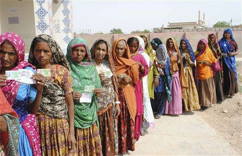 Pakistani women line up outside a polling station waiting to cast their ballots in Hyderabad, Pakistan, Saturday, May 11, 2013. Defying the danger of militant attacks, Pakistanis streamed to the polls Saturday for a historic vote pitting a former cricket star against a two-time prime minister and an unpopular incumbent. But attacks that killed and wounded dozens of people underlined the risks many people took just casting their ballots. (AP Photo/Pervez Masih) Photo: AP / AP