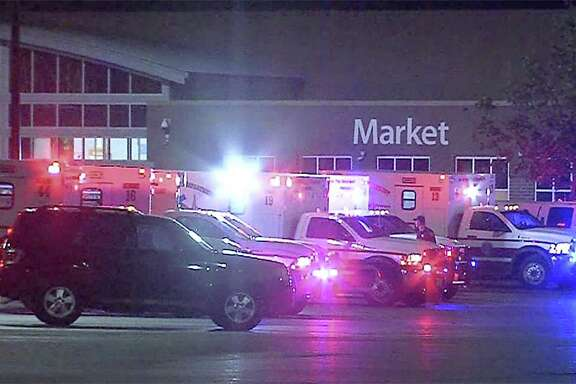 Emergency vehicles are seen in a parking lot at a Walmart located at IH-35 South and Palo Alto Road, Sunday. Authorities found 38 immigrants inside a tractor-trailer parked at the store. Eight were found dead and two died later. Seventeen were transported with life-threatening injuries.
