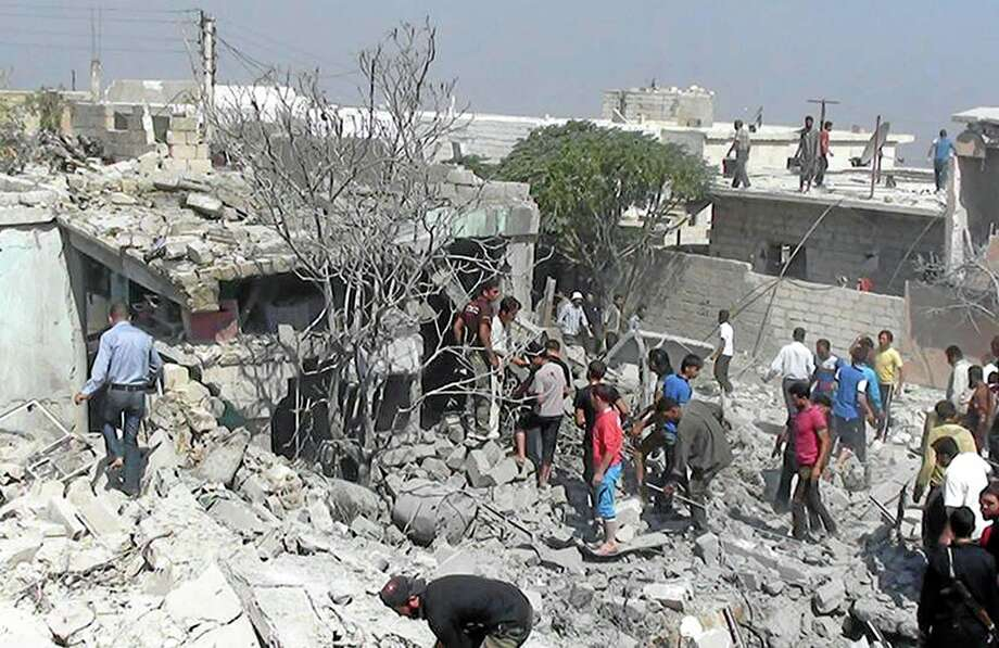 This citizen journalism image provided by Edlib News Network, ENN, which has been authenticated based on its contents and other AP reporting, Syrians search under rubble to rescue people from houses that were destroyed by a Syrian government warplane, in Idlib province, northern Syria, Friday, Aug. 30, 2013. United Nations experts are investigating the alleged use of chemical weapons in Syria as the United States and its allies prepare for the possibility of a punitive strike against President Bashar Assad's regime, blamed by the Syrian opposition for the attack. The international aid group Doctors Without Borders says at least 355 people were killed in the Aug. 21 attack in a suburb of Damascus, the Syrian capital.( AP Photo/Edlib News Network ENN) Photo: AP / EDLIB NEWS NETWORK ENN