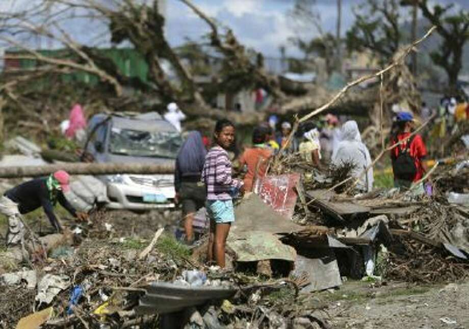 A typhoon survivor stands on rubbish in Tacloban, central Philippines on Sunday, Dec. 8, 2013.