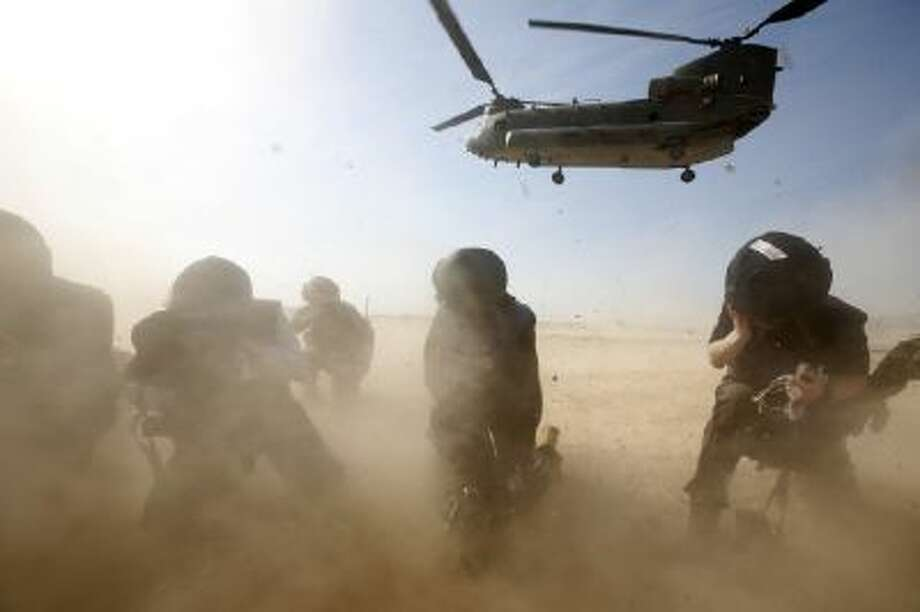 Media members protect themselves from dust as a helicopter lands successfully in Afghanistan on Dec. 16, 2013.