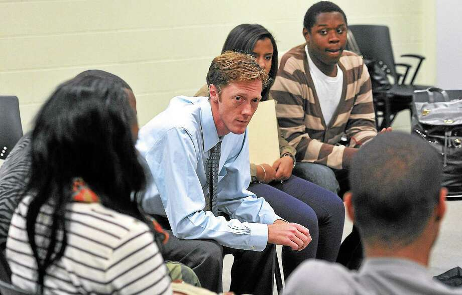 (Peter Casolino — New Haven Register)  Mayoral candidate Justin Elicker listens to youths at the Wilson Library in New Haven express their ideas about what the city need to do for it's youth. pcasolino@NewHavenRegister Photo: Journal Register Co.